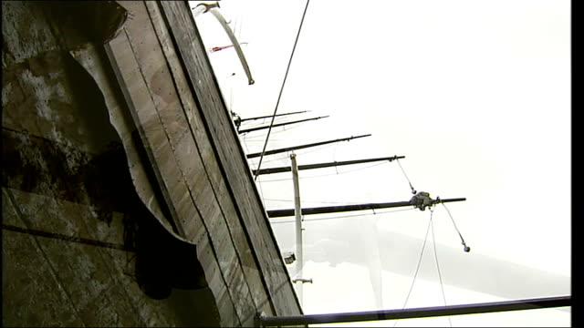 cutty sark restoration project underway low angle view man working on ship's rigging low angle view body of ship and mast above tilt down area around... - 船の一部点の映像素材/bロール