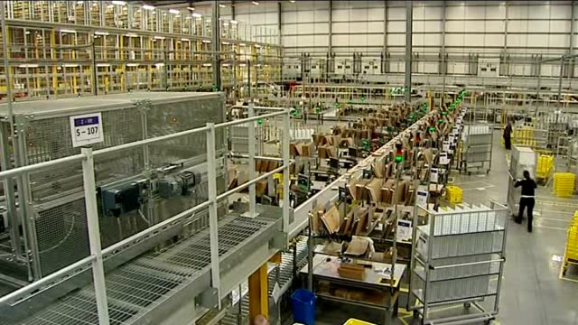 General views of Amazon warehouse ENGLAND Hertfordshire Amazon warehouse INT Amazon warehouse / Various of Allen Lyall watching crates of items...