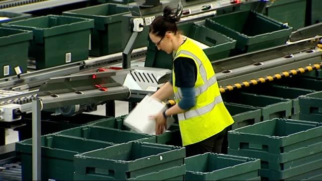 John Lewis distribution warehouse ENGLAND Buckinghamshire Milton Keynes INT Green boxes along on conveyor belt in John Lewis distribution warehouse /...