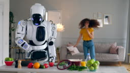 Cyborg and human concept. One robot cooks food while a woman dances.