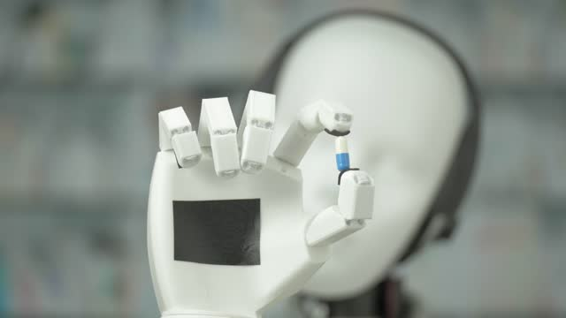 cyborg humanoid robot show a medicine capsule to a camera, rack focus, cu shot, loop able,. - machine learning stock videos & royalty-free footage