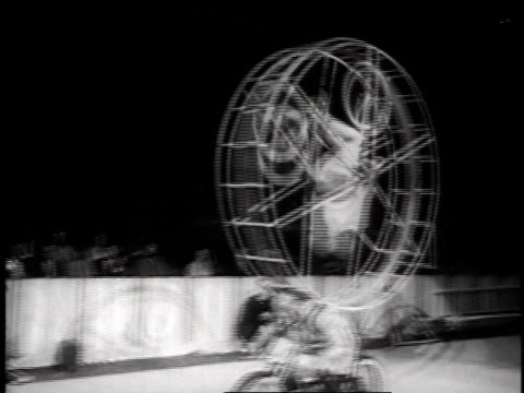 cycle act at circus in madison square garden, with bicyclist spinning in enclosed wheel atop motorcyclist's back / new york, usa - 1957 stock-videos und b-roll-filmmaterial