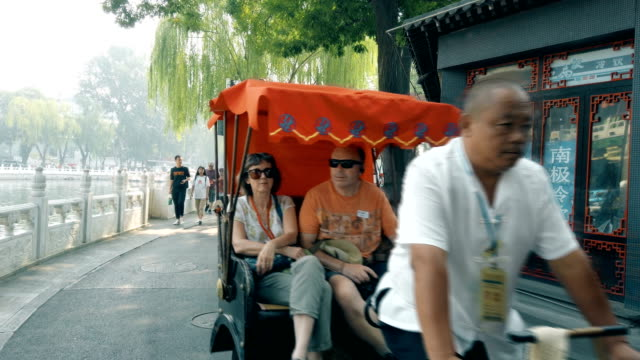 cycle rickshaw drivers taking tourists at houhai lakes area ,beijing, china - risciò video stock e b–roll