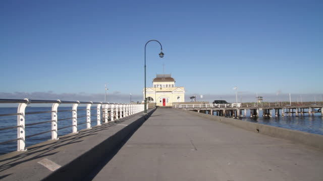 ws cycle rider riding cycle on bridge near st kilda pier pavilion / melbourne, victoria, australia - pavilion video stock e b–roll