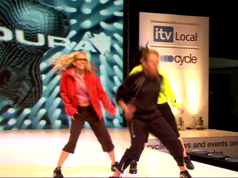 London Exhibition Centre INT Various shots of models/dancers modelling biker fashions on catwalk wearing bicycle helmets fluorescent jackets cycling...