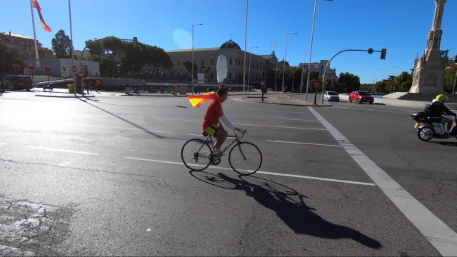 cycler rides at plaza de colón , with the columbus statue in the background, carrying a spanish flag during spain's national day, on october 12 in... - クリストファー コロンブス点の映像素材/bロール