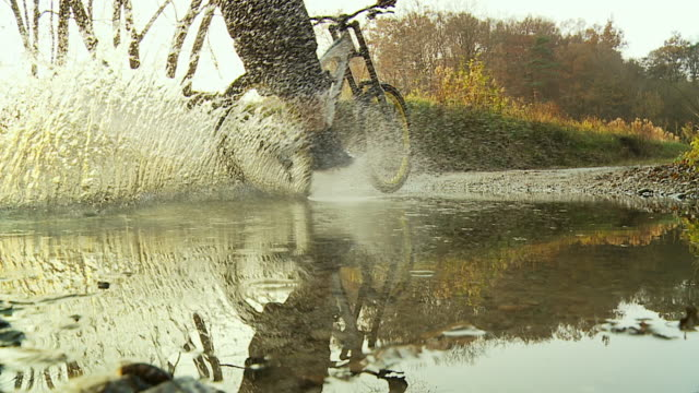 stockvideo's en b-roll-footage met hd slow motion: cycling fast through a puddle - springen