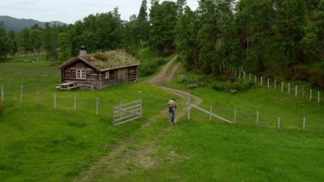自然の中でサイクリング。古い小屋。ドローンの視点 - 山小屋点の映像素材/bロール