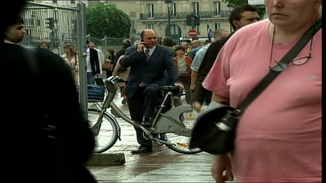 cycling loan sceme a success in paris; cutaways businessman standing holding hire bike whilst talking on mobile phone row of hire bikes in rack in... - financial accessory stock videos & royalty-free footage
