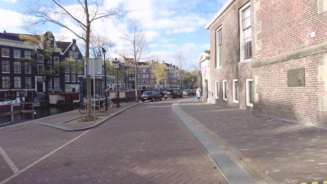 cycling past westerkerk and anna frank museum in amsterdam, holland - 4k auflösung stock-videos und b-roll-filmmaterial