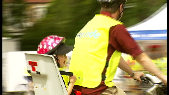 skyride 2010 event cyclists along in park young girl strapped into seat on back of bicycle smiling as along past reporter to camera - bicycle seat stock videos & royalty-free footage