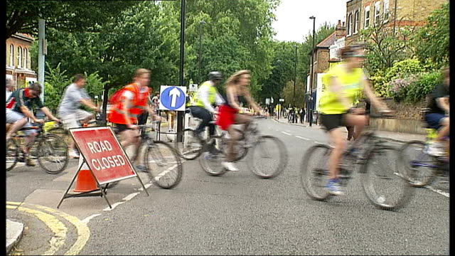 skyride 2010 event; england: london: ext cyclists participating in skyride event along street past road closed sign back view cyclists riding past... - road closed englisches verkehrsschild stock-videos und b-roll-filmmaterial
