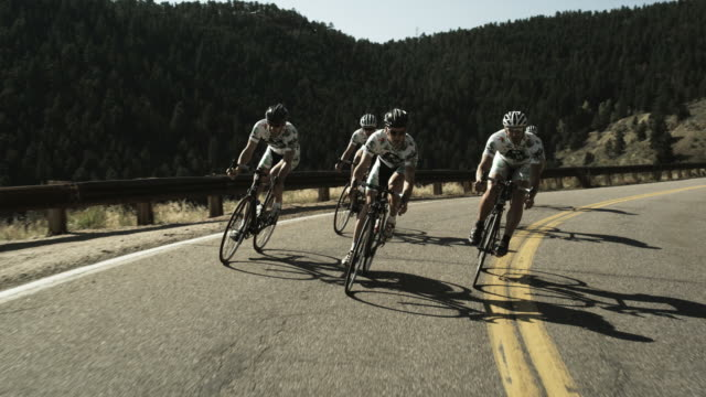 cycling team riding downhill in unison - elastane video stock e b–roll