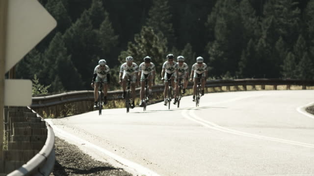 cycling team riding towards the camera in unison - elastane video stock e b–roll