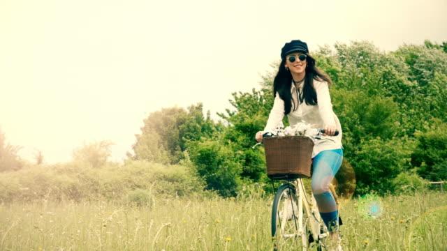 Mit dem Fahrrad aber Natur im Sonnenlicht. Mädchen in einen Hut und eine Sonnenbrille.