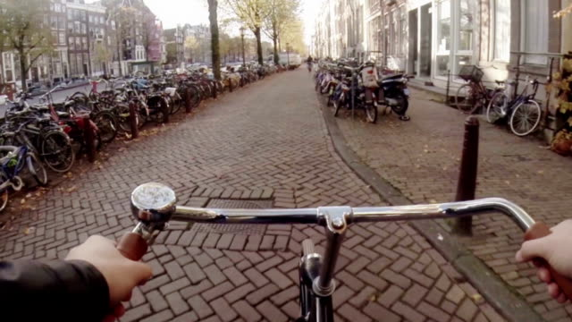 cycling through historic amsterdam centre - personal perspective stock videos & royalty-free footage