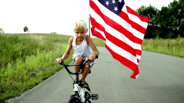 stockvideo's en b-roll-footage met cycling with flag of the usa - amerikaanse vlag