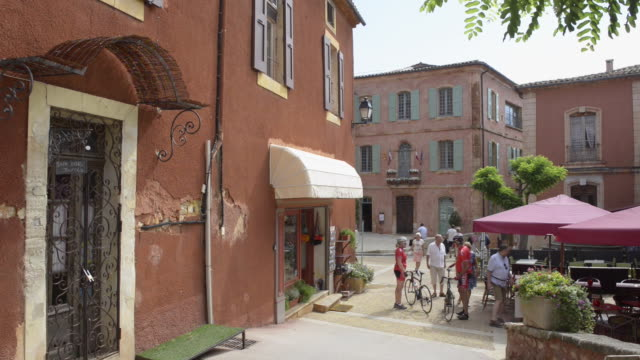cyclist and people on marketplace in ochre village roussillon - luberon video stock e b–roll