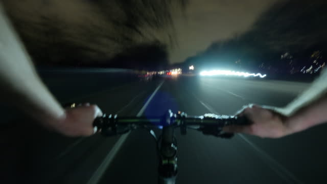 A cyclist POV at night travelling rapidly through the dark low lite outer Circle Road in Regents Park Central London