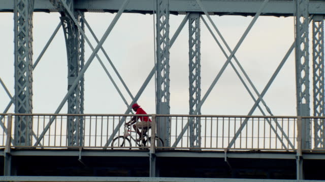 vidéos et rushes de a cyclist crossing john a roebling suspension bridge over ohio river, cincinnati, ohio - rivière ohio