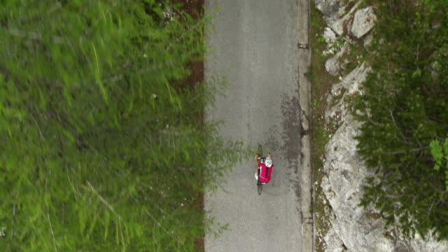 vidéos et rushes de cyclist cycling on the mountain road. - dessus