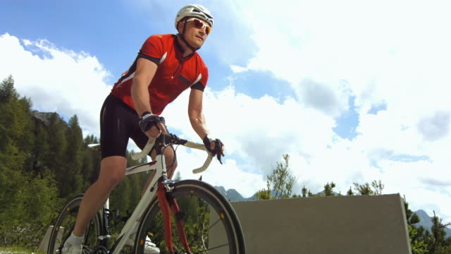 stockvideo's en b-roll-footage met cyclist cycling on the mountain road. - alleen één oudere man