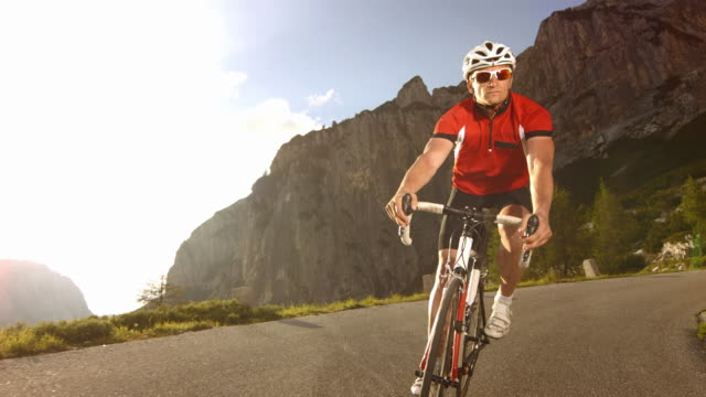 cyclist cycling on the mountain road. - curve stock videos & royalty-free footage