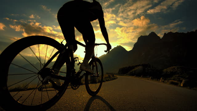 vídeos de stock, filmes e b-roll de cyclist cycling on the mountain road. - ciclismo
