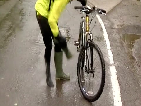 Cyclist empties one of his flooded boots