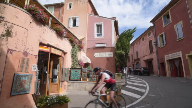 cyclist in old town in ochre village roussillon - luberon video stock e b–roll