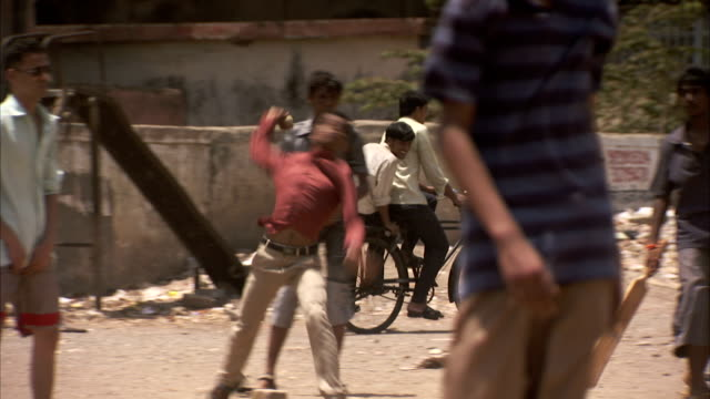 A cyclist passes a cricket game in the street in Mumbai. Available in HD