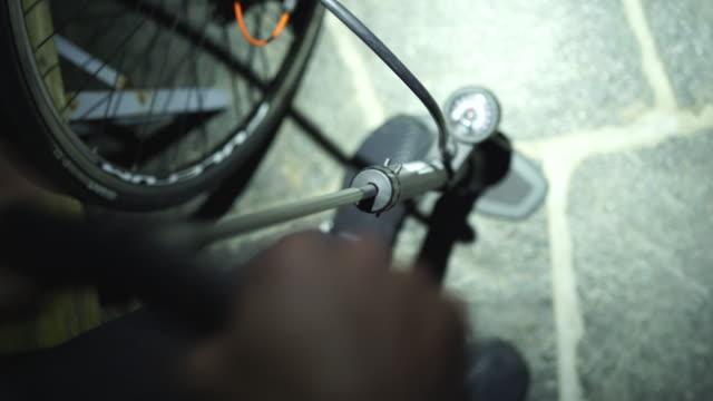 vídeos de stock, filmes e b-roll de ciclista que bombeia o ar nos pneus na obscuridade com um farol sobre - bomba de ar