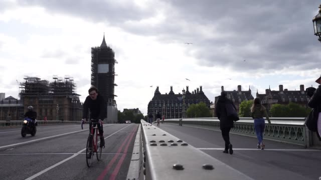 cyclist rides over westminster bridge and past big ben as they commute in london during the coronavirus covid-19 pandemic. the prime minister... - on the move stock videos & royalty-free footage