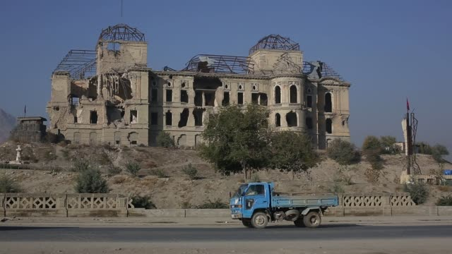 cyclist rides past the ruins of the iconic darulman palace, former home of the afghan king, later damaged in the civil war, in kabul, afghanistan,... - kabul stock videos & royalty-free footage