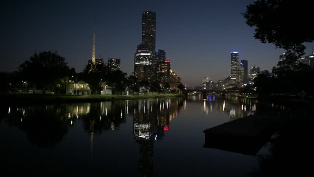 A cyclist rides through Birrarung Marr park as commercial buildings stand illuminated in the background at dusk in Melbourne Australia on Friday...