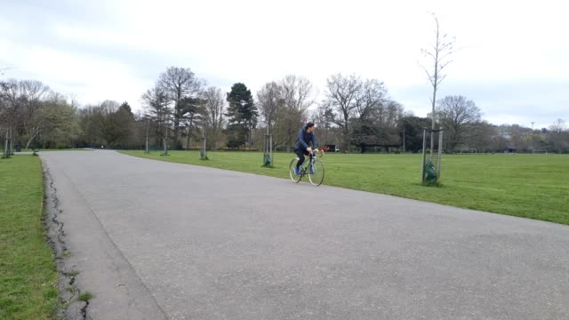 a cyclist rides through empty peckham rye park during the coronavirus pandemic on march 30 2020 in london england - brian dayle coronavirus stock videos & royalty-free footage