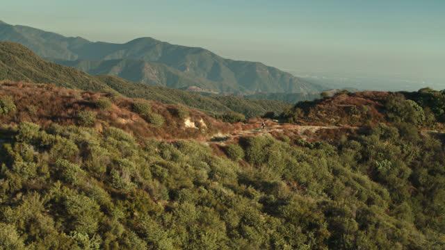 距離でサンガブリエルバレーとトレイルに沿ってサイクリスト - ドローンショット - 国有林点の映像素材/bロール
