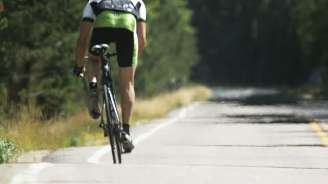 cyclist riding away from the camera - spandex stock videos & royalty-free footage