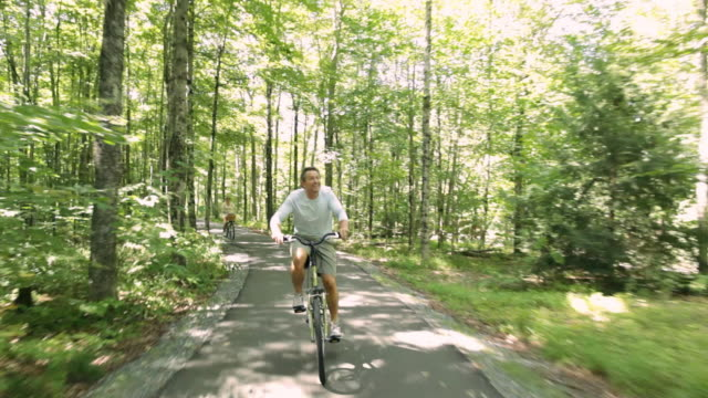 rear pov cyclist riding on a paved path through woods / stowe, vermont, united states - vermont stock-videos und b-roll-filmmaterial