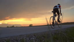 MS Cyclist riding on tranquil rural road at sunset