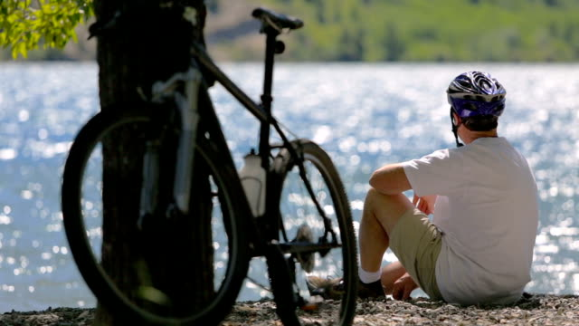 cyclist sits by picturesque lake - eyewear stock videos & royalty-free footage