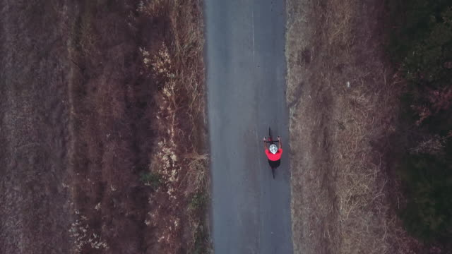 Cyclist training on road bicycle outdoor: drone aerial view