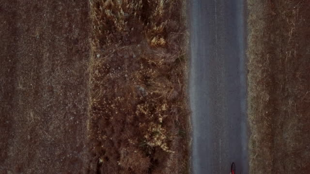 cyclist training on road bicycle outdoor: drone aerial view - racing bicycle stock videos & royalty-free footage