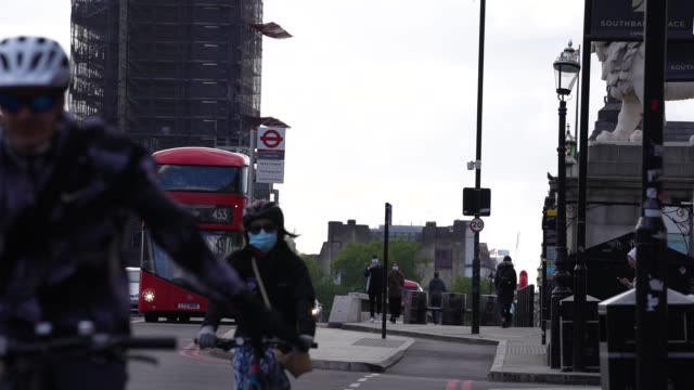 cyclist wearing a face mask rides over and past big ben as they commute in london during the coronavirus covid-19 pandemic. the prime minister... - on the move stock videos & royalty-free footage
