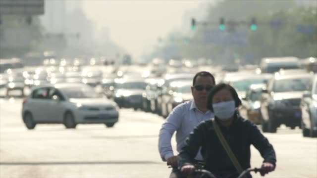 cyclist wearing air pollution prevention mask cycling along jamed cars in beijing, china - pechino video stock e b–roll