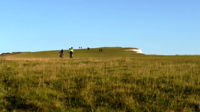 cyclists and hikers on the cliff top near beachy head, east sussex, uk - イーストサセックス点の映像素材/bロール