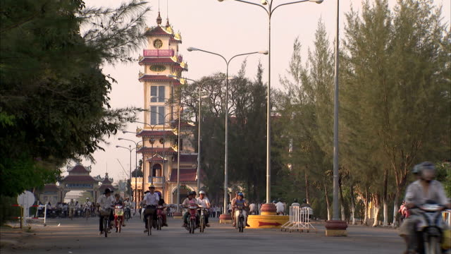 cyclists and motorcyclists move through a street in tay ninh. - tay ninh stock videos & royalty-free footage
