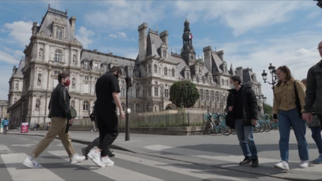 vidéos et rushes de cyclists and pedestians wearing protective face mask pass in ftont of paris city hall as france is slowly reopening after almost two months of strict... - piéton