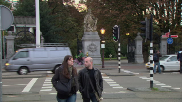 t/l ws cyclists and pedestrians crossing busy intersection, statue at entrance to park in background / amsterdam, holland - statue stock videos & royalty-free footage
