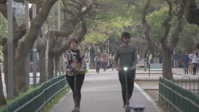 cyclists and pedestrians on rothschild boulevard, tel aviv, israel, middle east - 前ボケ点の映像素材/bロール